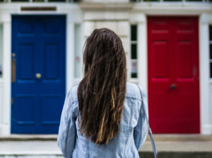 girl standing in front of two different doors