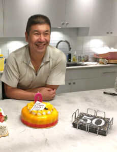 man satnding at counter with birthday cake