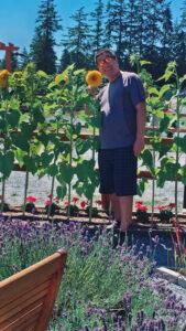 man standing by a sunflower